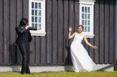 Неопознанный жених и невеста представляя перед известной черной церковью, Исландией Стоковые Изображения RF