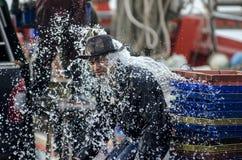 Неопознанный работник рыбацкой лодки моя на моле Стоковое Изображение RF