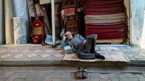 Неопознанный старик отдыхая в базаре внутри старого города, Турции Oturakci города Adiyaman историческом старом стоковое изображение rf