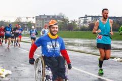 Неопознанный с ограниченными возможностями человек в марафоне на кресло-коляске на улицах города стоковые фото
