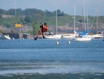 Неопознанный финский пловец спасения службы береговой охраны падает вниз к Балтийскому морю Стоковое Изображение