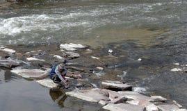 Неопознанный человек заполняя пластмасовый контейнер с водой пока сидящ на корточках на плоском валуне Река Южный Платт, весеннее стоковые изображения