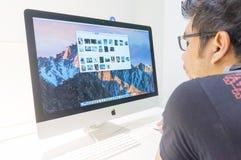 Неопознанный человек используя новый компьютер Яблока IMAC 27 Стоковые Фото