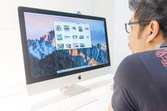 Неопознанный человек используя новый компьютер Яблока IMAC 27 Стоковая Фотография