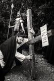 Неопознанный человек портретируя Иисус Христос носит большой деревянный крест во время reenactment распятия черная белизна стоковые изображения rf