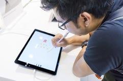 Неопознанный эскиз человека путем использование карандаша Яблока с новым Яблоком Ipad Pro Стоковая Фотография RF