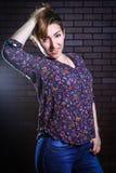 Неофициальная красивая женщина представляя против кирпичной стены Стоковые Фото