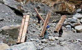 Непальские люди носят тяжелую древесину для конструкции в Гималаях стоковая фотография