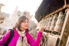 Непал - 4-ое января 2017:: женщина делает желание с колесом paryer Стоковое Изображение RF