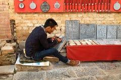 Непальский каменный гравер работая на виске Swayambhunath в Непале стоковое фото rf
