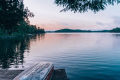 Неподвижное озеро во время захода солнца со шлюпкой на доке стоковое фото