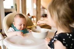 Непознаваемая девушка малыша дома подавая ее брат младенца Стоковые Изображения