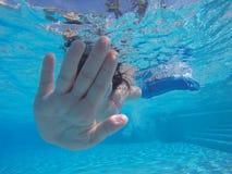 Непознаваемая девушка с заштукатуренной рукой плавая под водой в бассейне Стоковое Изображение RF