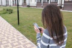 Непознаваемая женщина брюнет печатает сообщение на мобильном телефоне идя около дома задний взгляд стоковые фотографии rf