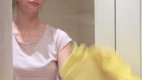 Непознаваемая женщина в желтых резиновых перчатках моя зеркало bathroom с желтым обтирает и уборщиком пены видеоматериал