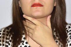 Непознаваемая женщина держит ее горло, боль в горле Стоковые Изображения