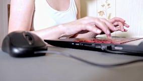 Непознаваемая женщина используя мышь и печатающ что-то на клавиатуре ноутбука, мелком фокусе сток-видео