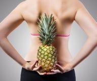 Непознаваемая женщина пригонки с ананасом стоковая фотография rf