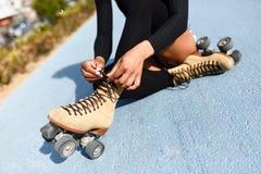 Непознаваемая черная девушка сидя на линии велосипеда и кладет дальше конек Стоковые Фото