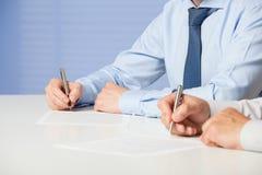 Непознаваемые бизнесмены подписывая контракт Стоковые Изображения RF