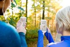 Непознаваемые идущие пары с умными телефонами и наушниками Стоковые Изображения