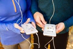 Непознаваемые идущие пары с умными телефонами и наушниками Стоковые Фото