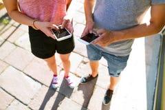 Непознаваемые молодые пары с smartphones на улице Стоковые Изображения