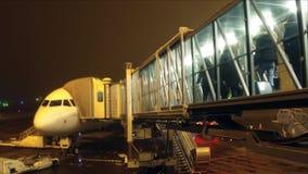 Непознаваемые пассажиры всходя на борт авиалайнера используя стеклянный мост двигателя на ноче Перемещение, отклонение, выходя ко Стоковое фото RF