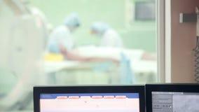Непознаваемые хирурги объединяются в команду выполняющ деятельность в операционной больницы Пациент хирурга работая видеоматериал