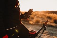Непознаваемый буфет воды удерживания велосипедиста на велосипеде на a вниз со скалистого холма на заходе солнца Весьма концепция  стоковое фото