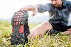 Непознаваемый молодой бегун сидя на траве, протягивая ногу стоковое фото rf