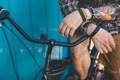 Непознаваемый молодой человек сидя на велосипеде около концепции голубого образа жизни предпосылки стены ежедневного городской от Стоковая Фотография RF