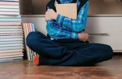 Непознаваемый семилетний мальчик сидя среди книг Стоковое Фото