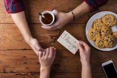 Непознаваемый укомплектовывает личным составом и руки женщины Валентайн сообщения габаритов карточек романтичное 6 Чай и печенья Стоковое фото RF