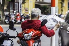 Непознаваемый человек в красной рубашке читает газету, сидит на sco стоковое изображение rf