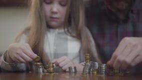 Непознаваемый человек в рубашке и меньшая сконцентрированная девушка сидя на таблице считая монетки близко вверх Отец и видеоматериал