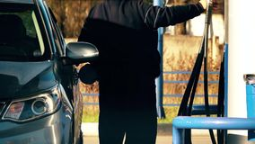 Непознаваемый человек дозаправляя его автомобиль на бензоколонке Стоковая Фотография