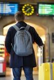 Непознаваемый человек на платформе железнодорожной станции смотря на информационном дисплее Стоковые Изображения RF