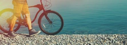Непознаваемый человек hiker идя на утро побережья с его велосипедом стоковое изображение rf