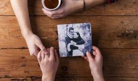 Непознаваемый человек держа руку женщины Смотреть их фото Пара Стоковое Изображение RF