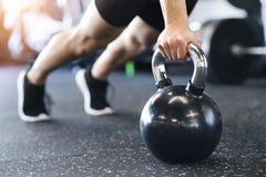 Непознаваемый человек пригонки в делать спортзала нажимает поднимает на kettlebells стоковое фото rf