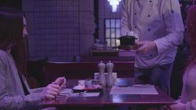 Непознаваемый шеф-повар приносит еду для 2 девушек сидя на таблице в ночном клубе или ресторане в голубом свете видеоматериал