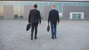 2 непознаваемых молодых бизнесмена в официально носке идя с портфелями к центру офиса Уверенно идти менеджеров акции видеоматериалы