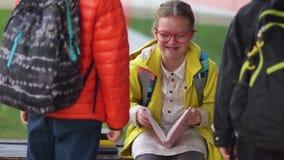 2 непознаваемых подростка причаливают скромной девушке со стеклами сидя на стенде Школьница внезапно смеется вне громко акции видеоматериалы