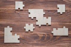 Неполные деревянные головоломки на коричневом деревянном столе, взгляд сверху, плоское положение стоковое фото