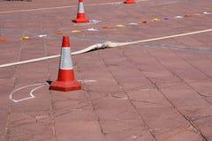 Непредвиденный триангулярный оранжевый конус обозначая опасность и пожарный рукав лежат на каменном поле, дороге стоковая фотография