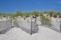 Непрерывные линии загородки пляжа, с травой пляжа и голубым небом стоковые изображения