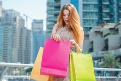 Непредвиденное приобретение Маленькая девочка держа хозяйственные сумки и surpri Стоковое фото RF