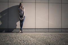 Непринужденный стиль женщины против каменной стены grunge Стоковые Изображения