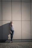 Непринужденный стиль женщины против каменной стены grunge Стоковые Фото